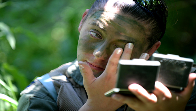 Capt. Stephanie Bradford, 37th Bomb Squadron pilot, applies camouflage face paint during Survival, Evasion, Resistance and Escape training near Fort Meade, S.D., June 21, 2016. The objective of this training is to prepare aircrew to improve their skills to survive in the wilderness, relocate to a safe area undetected, and await friendly forces to rescue them. (U.S. Air Force photo by Senior Airman Rebecca Imwalle/Released)
