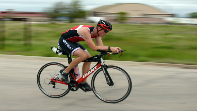 First Lt. Corey Hayes, 28th Force Support Squadron food service officer, endures the biking portion of a triathlon at Ellsworth Air Force Base, S.D., May 21, 2016. Being a big proponent of physical fitness, Hayes avidly participates in triathlons such as these to inspire others to set goals and work towards them. (U.S. Air Force photo by Airman Donald Knechtel/Released)