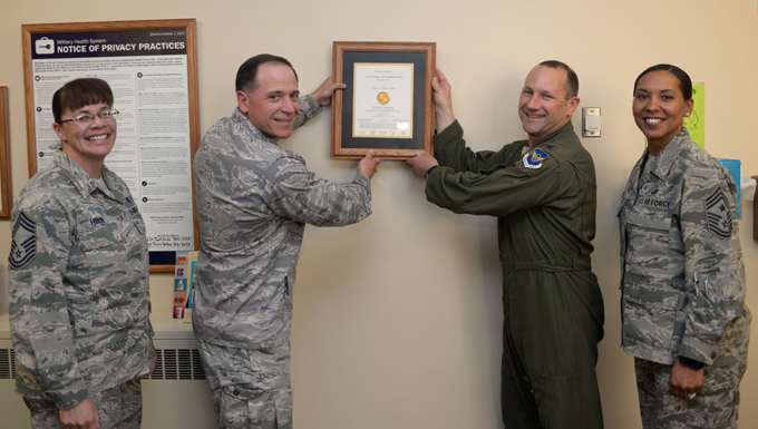 Col. Gentry Boswell, 28th Bomb Wing commander, center right, and Col. Christopher Dun, 28th Medical Group commander, center left, are joined by Chief Master Sgt. Sonia Lee, 28th BW command chief, right, and Chief Master Sgt. Tracy House, 28th MDG superintendent, left, to hang a Joint Commission accreditation certificate in the 28th MDG lobby at Ellsworth Air Force Base, S.D., May 26, 2016. The Joint Commission, an independent, not-for-profit organization, accredits and certifies nearly 21,000 health care organizations and programs in the U.S. Accreditation from the Joint Commission is recognized as a sign of quality that reflects an organization's commitment to meeting certain performance standards. (U.S. Air Force photo by Airman Donald Knechtel/Released)